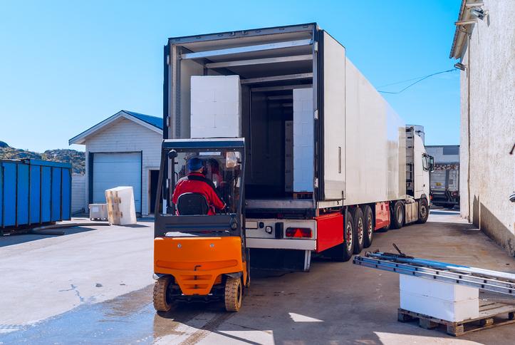 Worker on the loader loads long white semi-truck